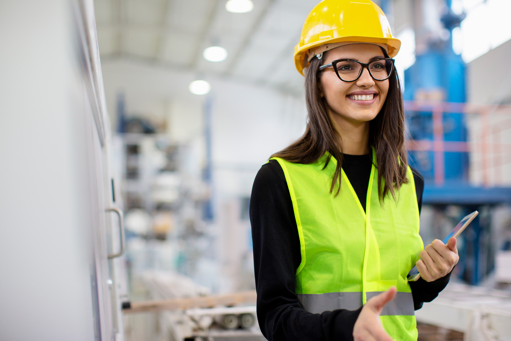 Microsoft F1 Firstleine or Frontline Worker, female with glasses smiling while wearing a yellow hard hat.